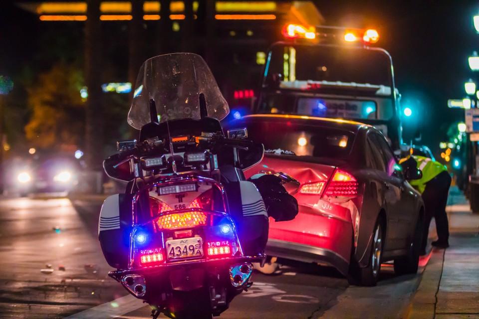 גרר מעלה מכונית שעברה תאונה ואופנוע משטרה עומד מאחורי